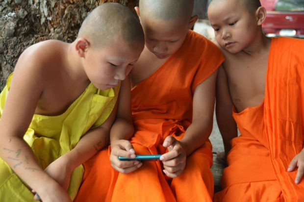 Boy Monks Playing on A Smartphone