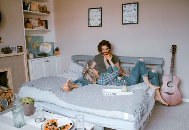 Couple Eating Pizza In Bed