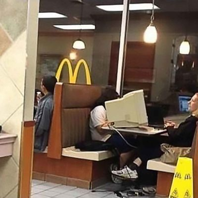 Woman Using Desktop Computer In A McDonalds Restaurant Booth