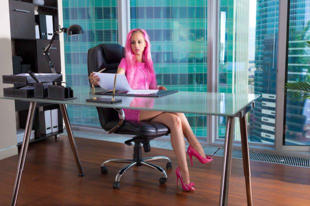 Woman Working Behind A Desk In A Pink Dress